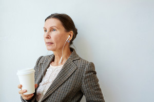 Aged female with hot drink listening to music or lecture