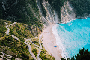 Alone tourist tent on famous Myrtos Beach. Big foam waves rolling towards the bay. Kefalonia, Greece