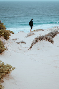 Alone traveler in snow-white dune landscape on the Atlantic coastline
