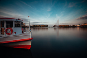 Alster Lake with traditional steamer boat for cruise on the water in Hamburg, Germany. Long exposure cityscape