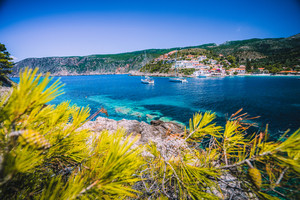 Amazing Assos village, Kefalonia. Greece. White cruise yachts staying at anchor in beautiful emerald green colored lagoon water. Framed by pine trees branches