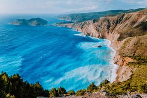 Amazing coastline landscape near Assos village. Sea waves rolling to shore cliffs on the beach. Kefalonia, Ionian islands, Greece