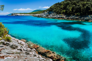 Amazing colorful bay on Mediterranean island. White cliffs overgrown with vegetation. Summer vacation