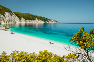 Amazing Fteri beach lagoon, Cephalonia Kefalonia, Greece. Tourists under umbrella relax near clear blue emerald turquise sea water. White rocks in background