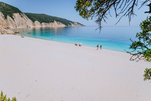 Amazing Fteri beach lagoon, Kefalonia, Greece. Tourists under umbrella chill relax near clear blue emerald turquoise sea water. Cliff rock coastline in background