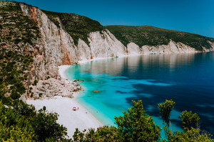 Amazing Fteri beach lagoon, Kefalonia, Greece. Tourists under umbrella chill relax near clear blue emerald turquoise sea water