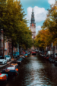 Amazing Groenburgwal canal in Amsterdam with the Soutern church Zuiderkerk at sunset in autumn