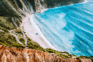 Amazing Myrtos beach with rolling waves. Beautiful coastline, cliffs surrounded the sea bay of blue water, Kefalonia, Ionian islands, Greece