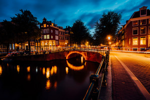 Amazing night in Amsterdam. Illuminated canal and bridge with typical dutch houses and bicycles, Holland, Netherlands. Lights trails from the bicycles. Long exposure