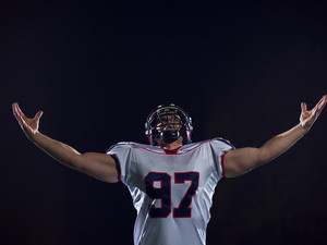 american football player celebrating after scoring a touchdown on field at night