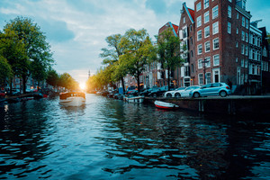 Amsterdam beautiful tree-lined canal with cruise boat in warm sunset light