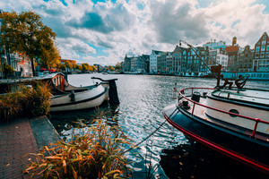 Amsterdam canal Singel with typical dutch houses and houseboats during sunny autumn day. Golden trees and amazing cloudscape. Holland, Netherlands