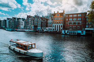 Amsterdam Netherlands dancing houses over river Amstel landmark in old european city landscape. Picturesque clouds on sunny autumn day