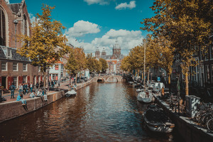 AMSTERDAM, THE NETHERLANDS - September 09, 2018: Canal and St. Nicolas Church in Amsterdam, Netherlands in an autumn day. Tourists relaxing on the banks of canal. Vacation in Europe