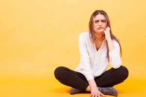 Angry girl looking at the camera and sitting down over yellow background. Upset girl m