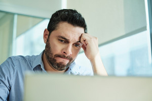 Angry Hispanic businessman working with laptop computer in office, losing patience. Anxious executive man under stress at work for technology problems and software pc virus.