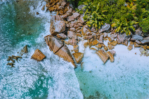 Anse Cocos beach tropical island La Digue Seychelles. Drone aerial view of foam ocean waves rolling towards the rocky coastline and palm trees