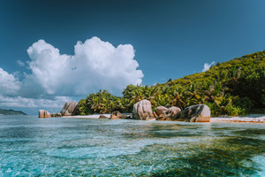 Anse Source d'Argent - Cloudscape over paradise beach with bizarre rocks and shallow lagoon water on La Digue island in Seychelles