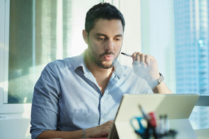 Anxious hispanic man at work as employee with laptop computer, looking at monitor and smoking electronic cigarette as an anti-stress remedy. Ex-smoker using e-cigarette to vape instead of smoking.