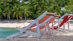 Appealing Beach Chairs on Sand. Palm Trees and Ocean in Background. Haad Salat. Ko Phangan, Thailand