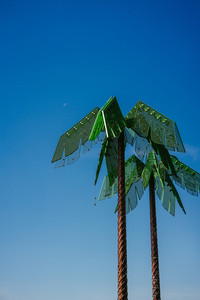 Artificial green metal palms with blue sky background in Park Fiction Hamburg. An artistic and sociopolitical project located in small park near St. Pauli, Hamburg