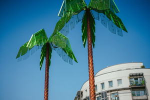 Artificial green metal palms with white living house and blue sky background in Park Fiction Hamburg. An artistic and sociopolitical project located in small park near St. Pauli, Hamburg