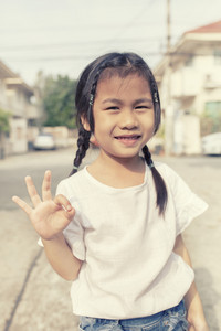 asian children hand sign all right with smiling face outdoor