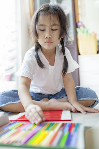 asian children playing color pencil in hoime living room