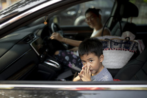asian children sitting on passenger seat and go to school with mother