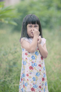 asian children use hand close her nose standing in green garden