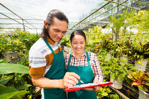 Asian couple reading names of plants in the greenhouse