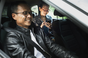 asian man driving passenger car and woman with smart phone in hand toothy smiling with happiness face