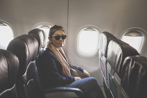 asian single woman on passenger seat of airplane