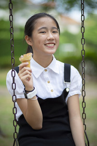 asian teenager eating icecream cone with happiness face in green park