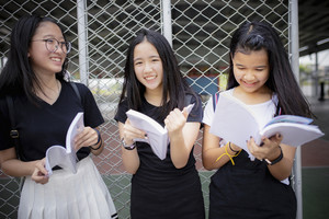 asian teenager holding school book and laughing with happiness emotion standing outdoor