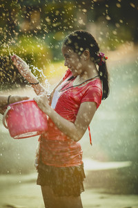 asian teenager playing water in songkarn day festival thailand