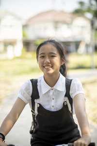asian teenager riding bicycle with happiness emotion in public park