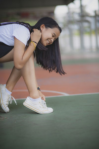 asian teenager wearing sneaker shoe in indoor sport club