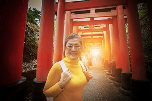 asian tourist toothy smiling face in  fushimi inari shrine one of most popular traveling destination in kyoto japan