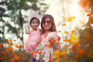asian woman and little girl happiness emotion in yellow cosmos flower blooming field