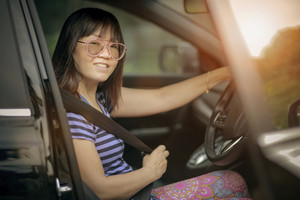 asian woman driving personal car toothy smiling face