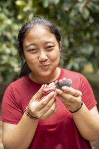 asian woman eating fresh mangosteen in fruit plantation field