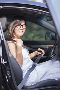 asian woman fasten car seat belt before take a driving