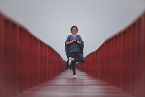 asian woman playing yoga pose on red wooden bridge