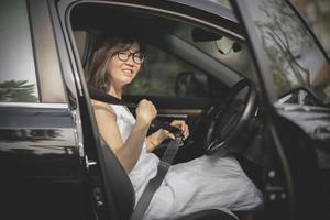 asian woman sitting in driver seat of sedan car fasten safety seat belt