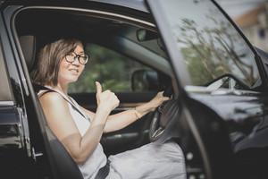asian woman sitting on driver seat in suv car sigh good tumb