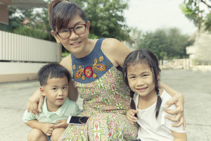 asian woman toothy smiling face happiness emotion  taking a photo with two children on location