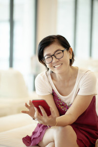asian woman toothy smiling face in living room while using smart phone and internet connect
