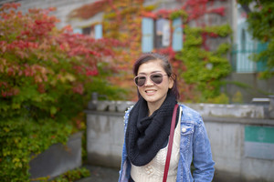 asian woman toothy smiling face with colorful leaves park background