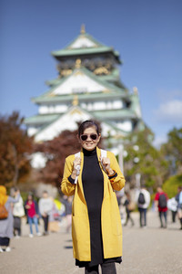 asian woman tourist taking a photograph at osaka castle one of most popular traveling destination in japan